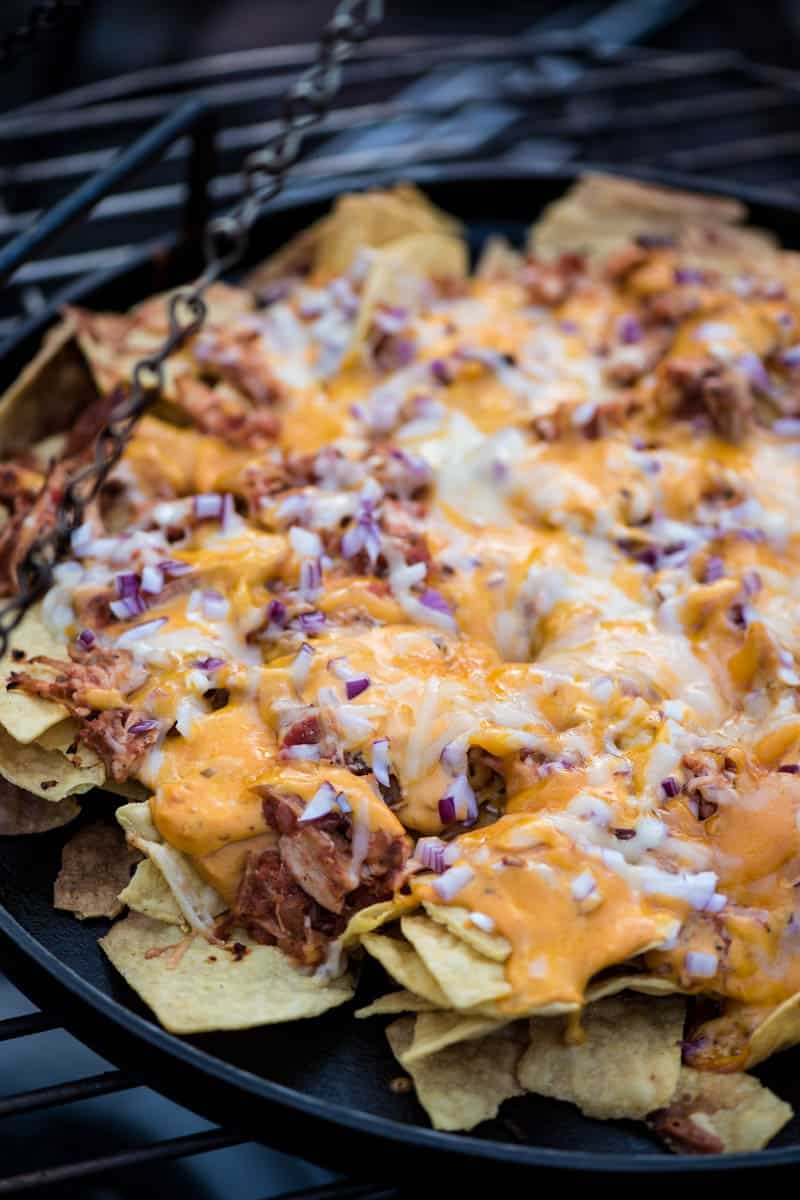 campfire nachos with chicken cooking on a cast iron griddle on a tripod grill over the campfire