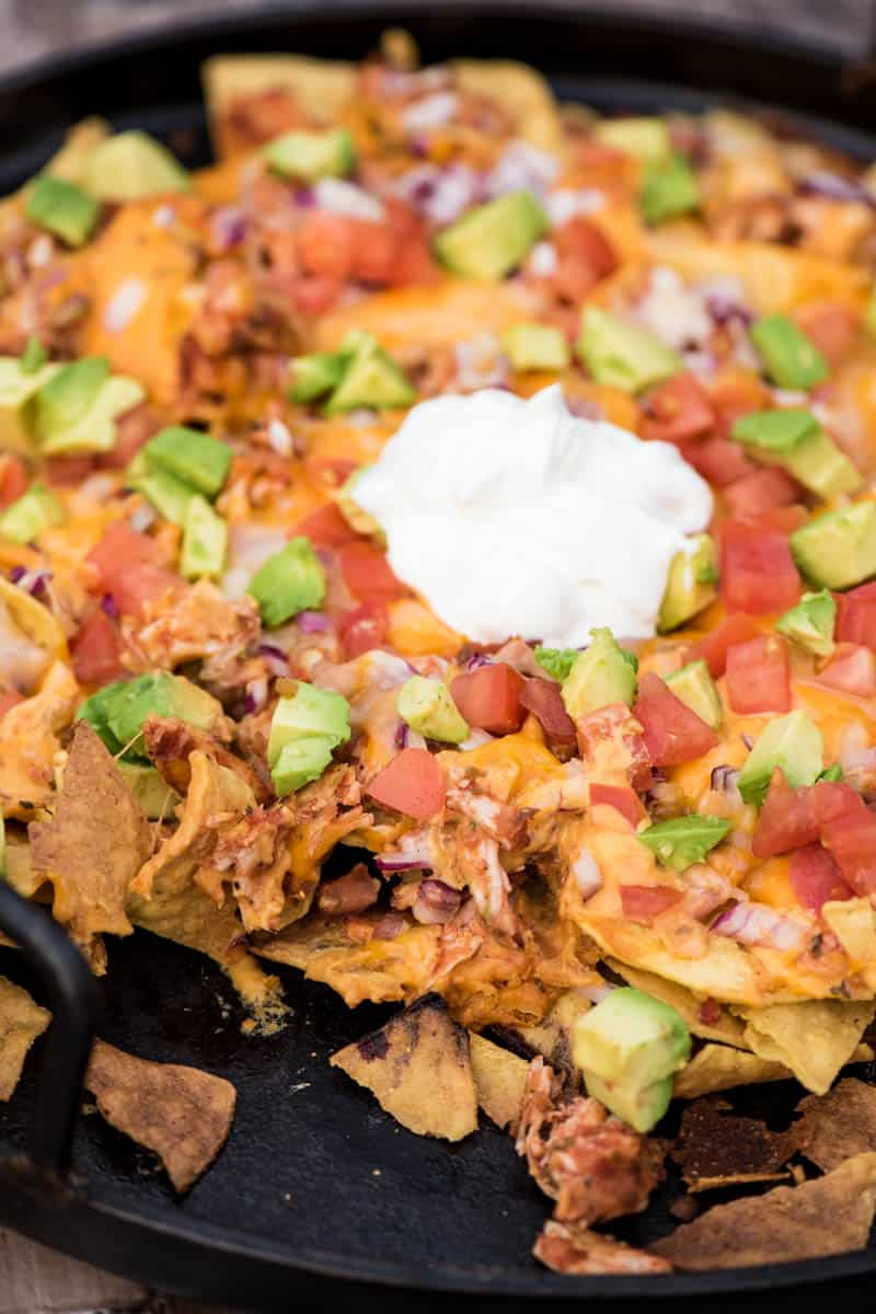 loaded camping nachos with chicken, Roma tomatoes, avocados, and sour cream