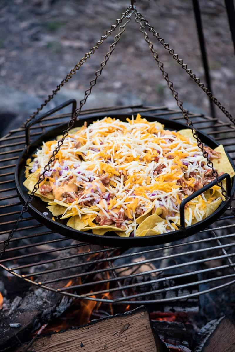 cooking chicken nachos over the campfire on a large cast iron griddle