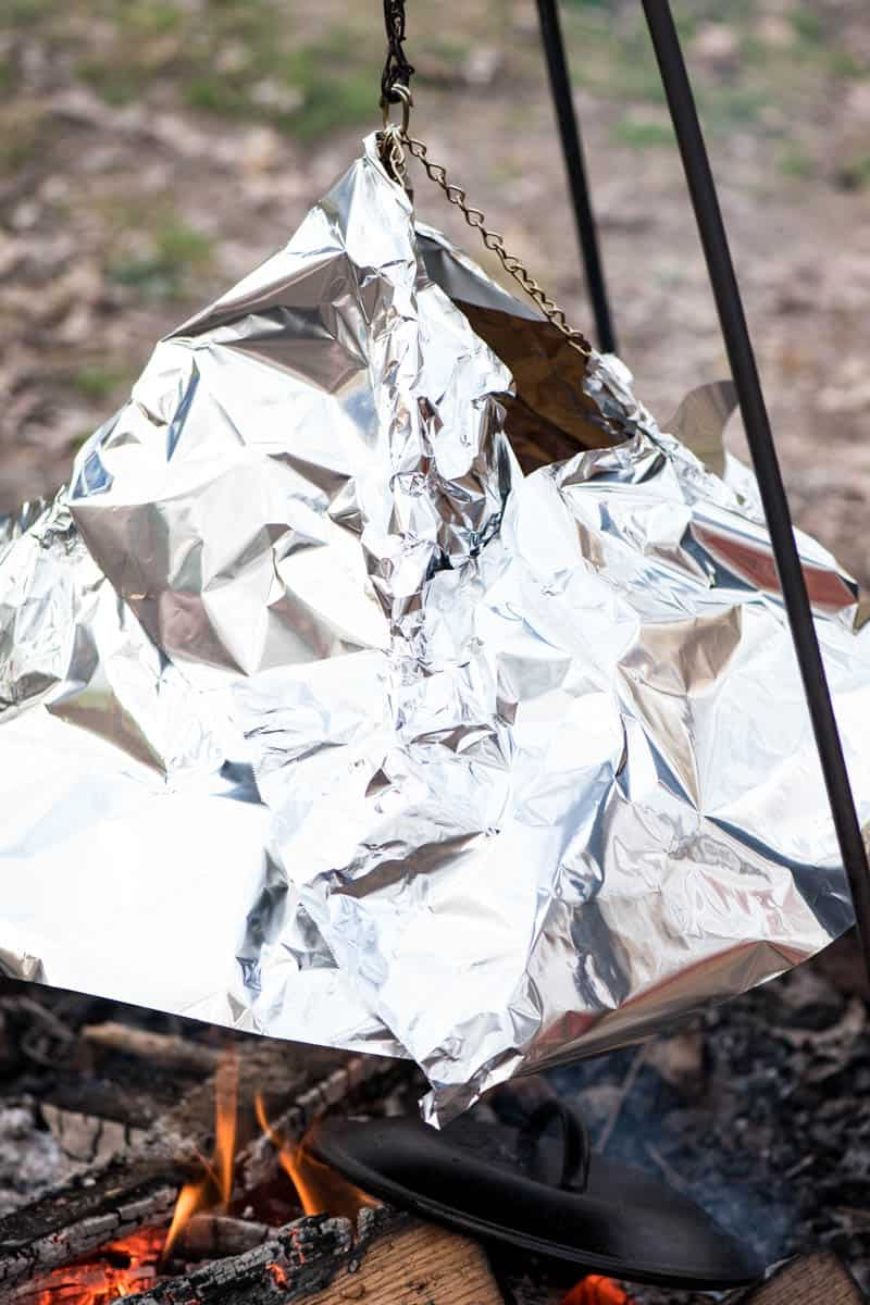 using aluminum foil to act as an oven tent, trapping heat for chicken nachos recipe over the campfire