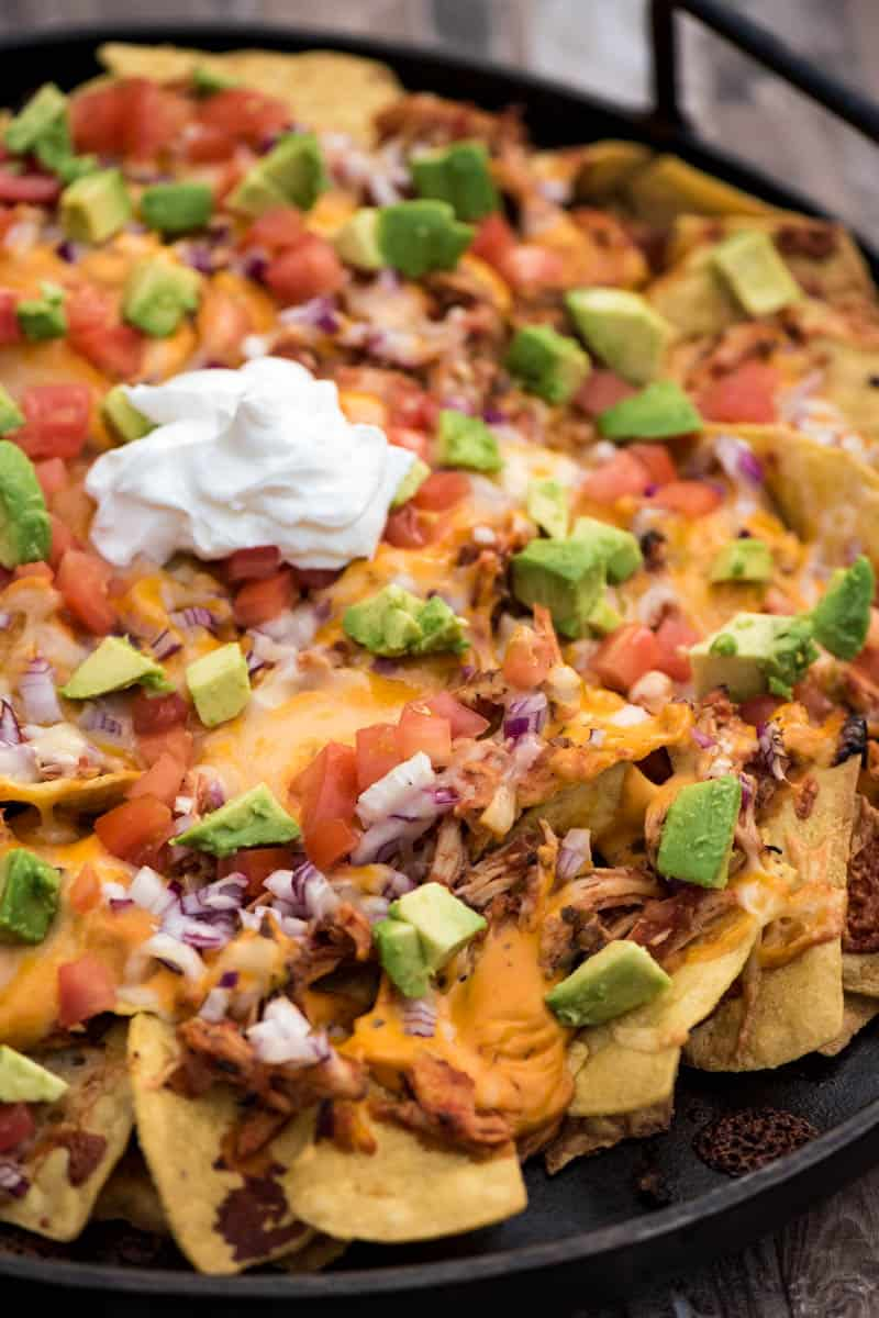loaded chicken nachos in cast iron pan