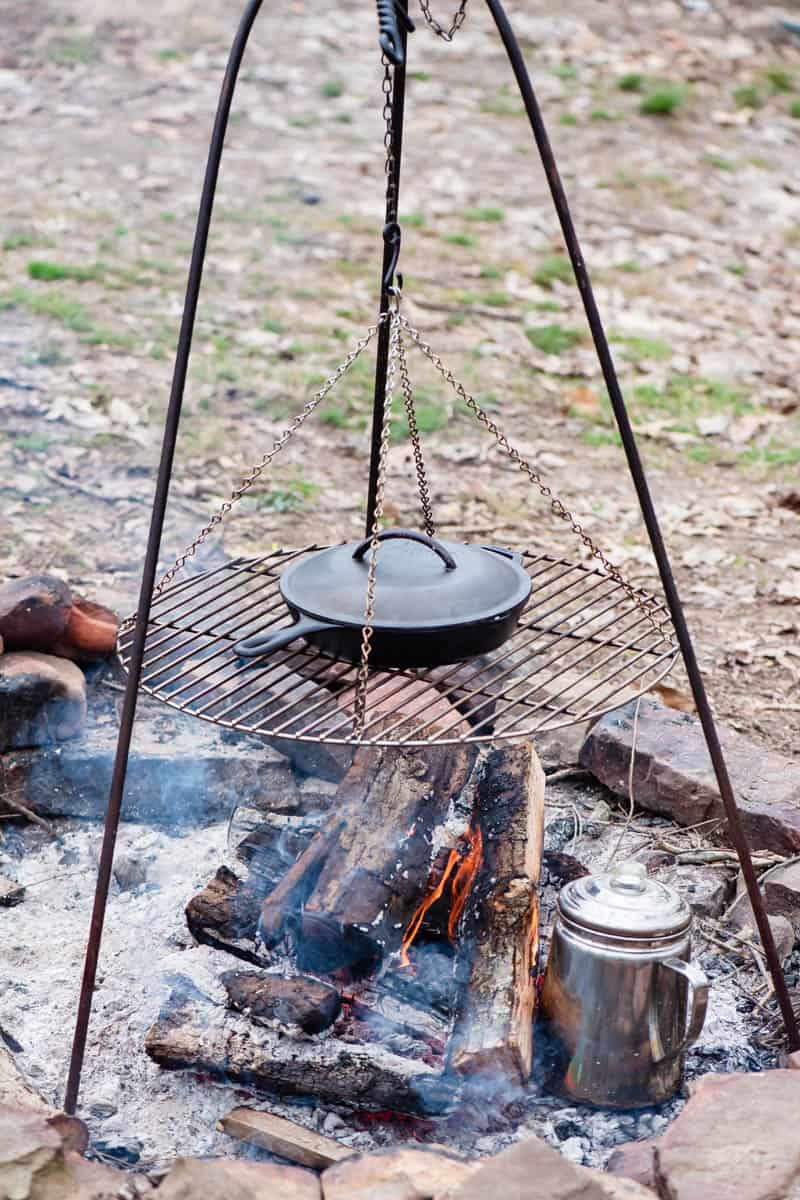 camping kitchen essentials, including tripod grill with cast iron skillet over campfire