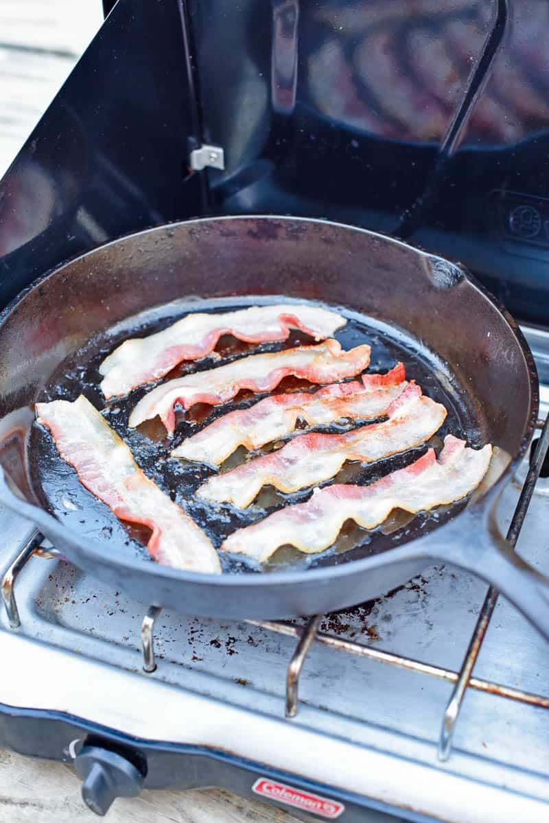 cooking bacon in a cast iron skillet on a camp stove