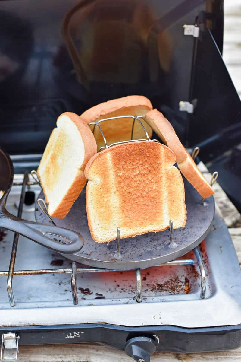 camping cooking equipment, including camp stove, cast iron skillet, and camp stove toaster with bread toasting