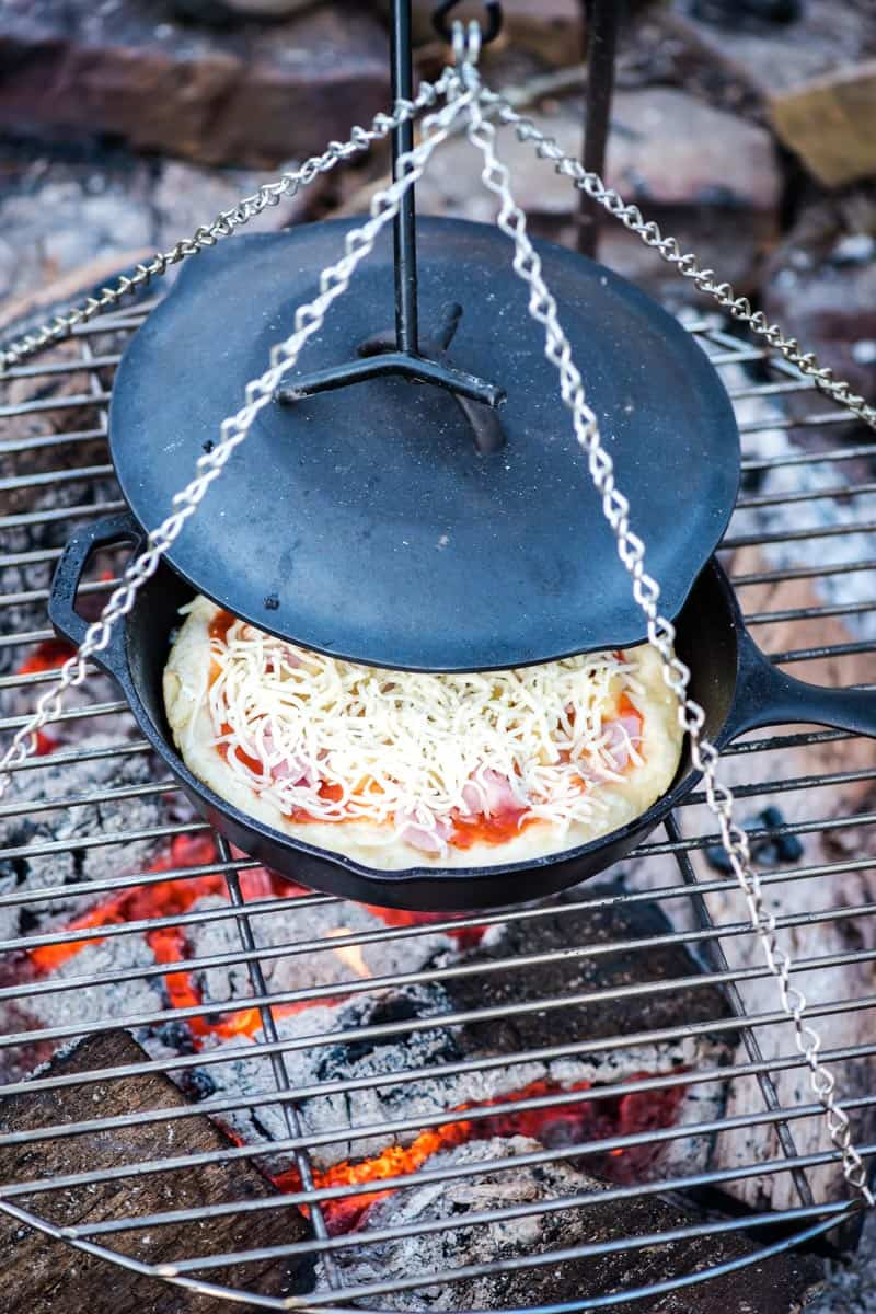making campfire pizza from scratch in cast iron skillet over campfire