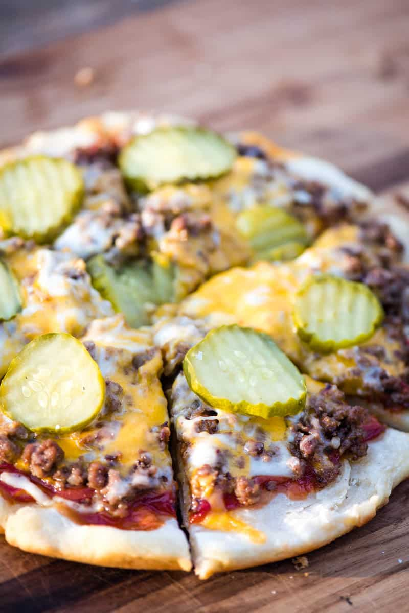 sliced hamburger pizza on a wooden cutting board