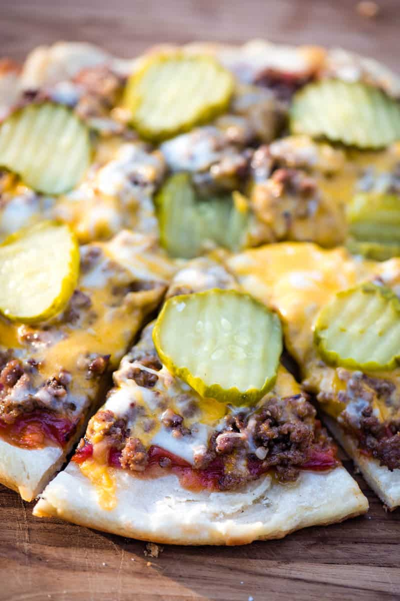 sliced hamburger pizza with pickles and melted cheese on a wooden cutting board