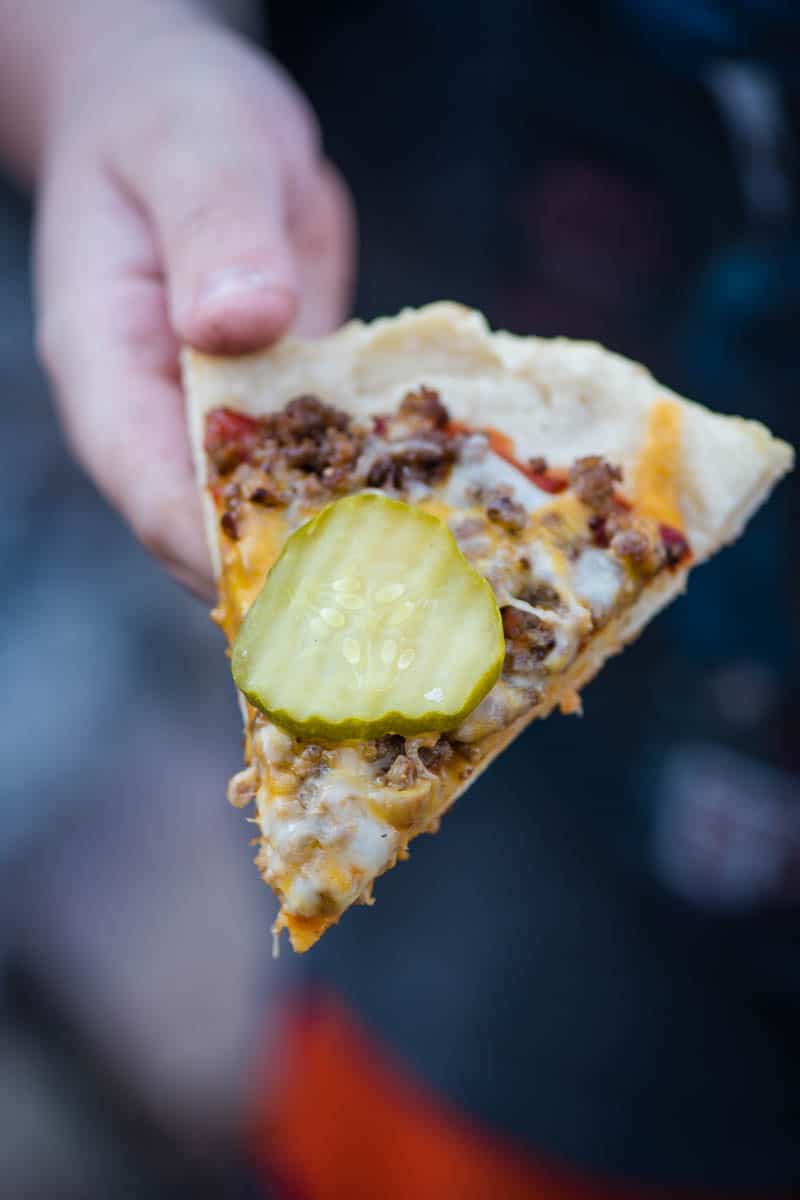 hand holding slice of homemade grilled cheeseburger pizza