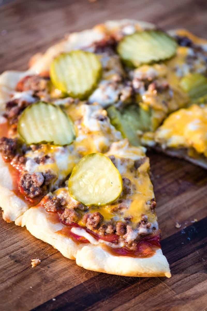 sliced cheeseburger pizza with one slice missing on wooden cutting board