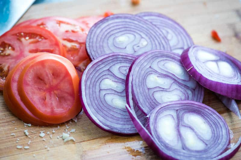 sliced tomatoes and red onions on cutting board for cheeseburger recipe