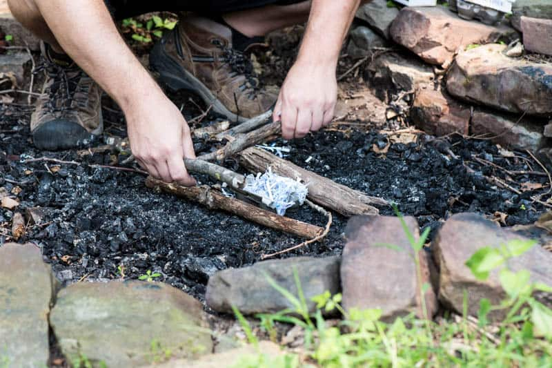 man starting a fire with a homemade fire starter in fire pit
