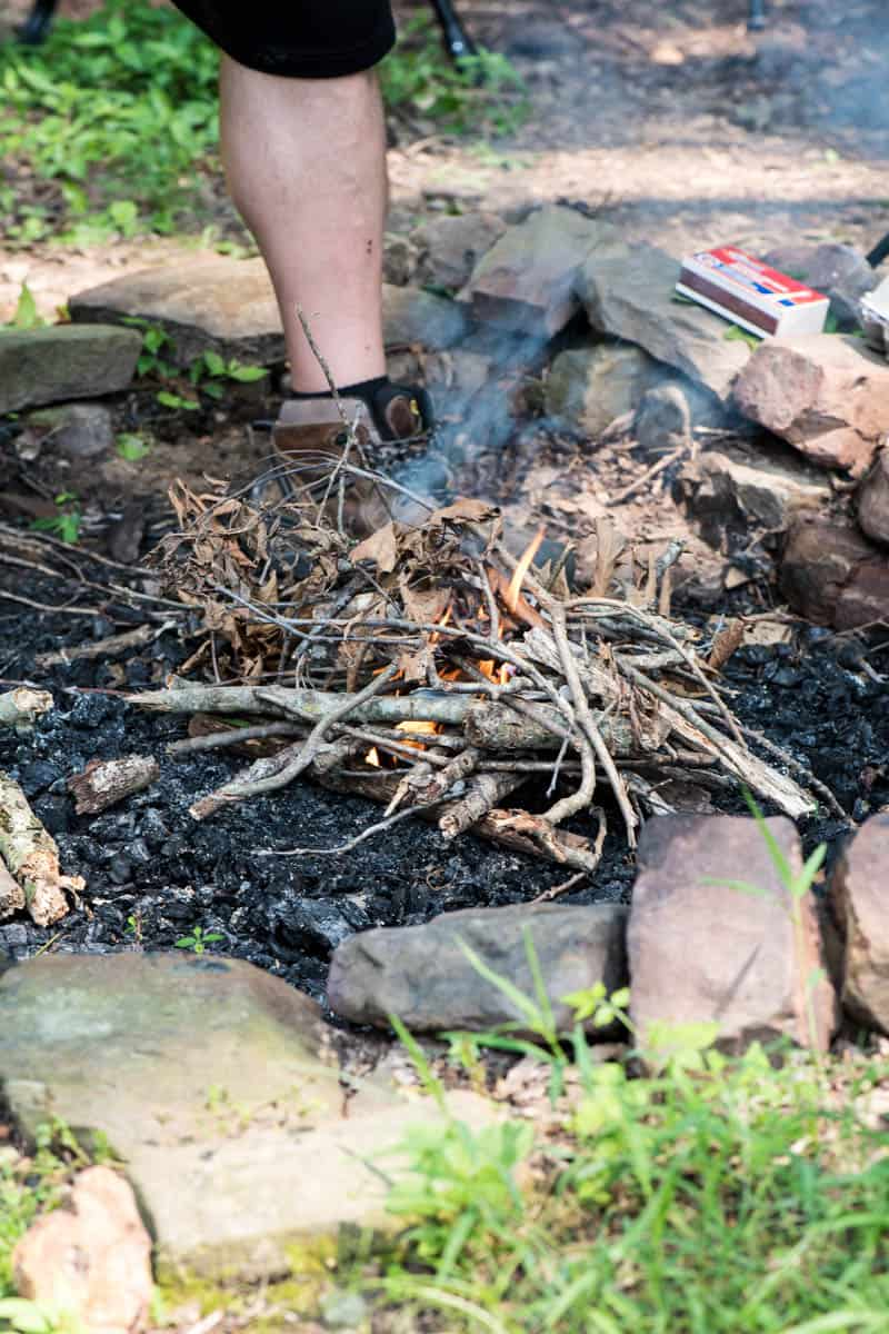 man adding kindling to easy fire starter in campfire pit