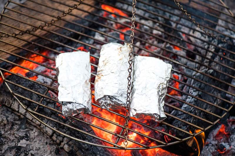 grilling camping breakfast burritos in heavy duty foil on a tripod grill over the campfire
