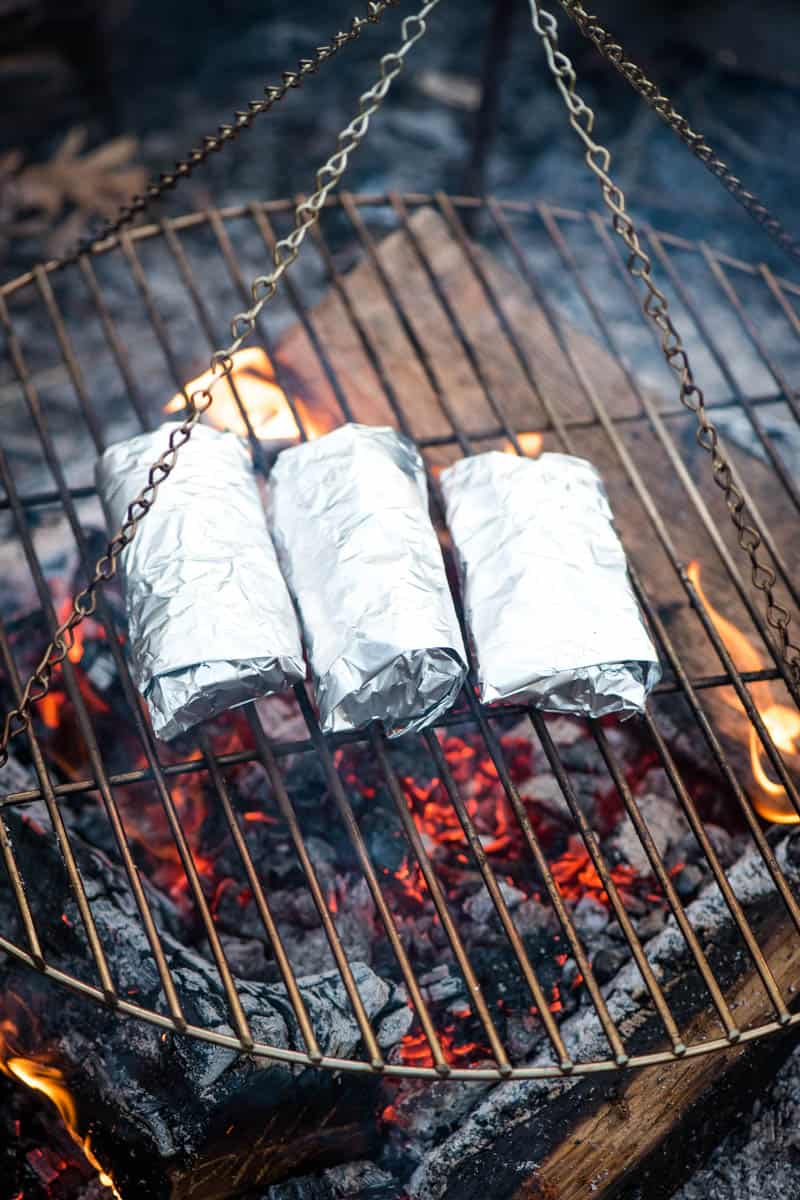 cooking campfire breakfast burritos in foil over the campfire on a tripod grill