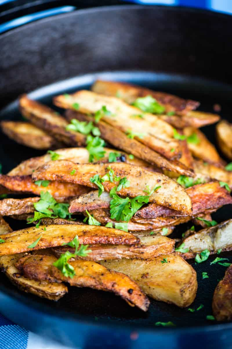golden brown steak cut fries, sprinkled with parsley, in cast iron skillet