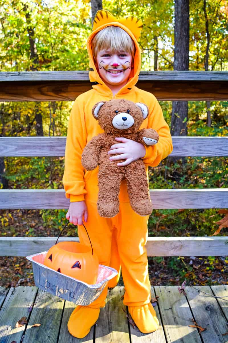 boy in Garfield Halloween costume with Pooky the Teddy Bear and lasagna pan with trick or treat bucket