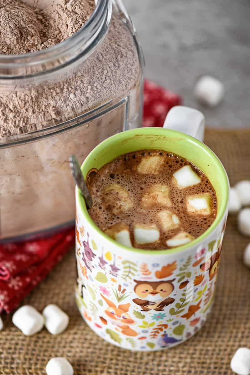 hot cocoa mix made into homemade hot cocoa in mug with spoon and mini marshmallows