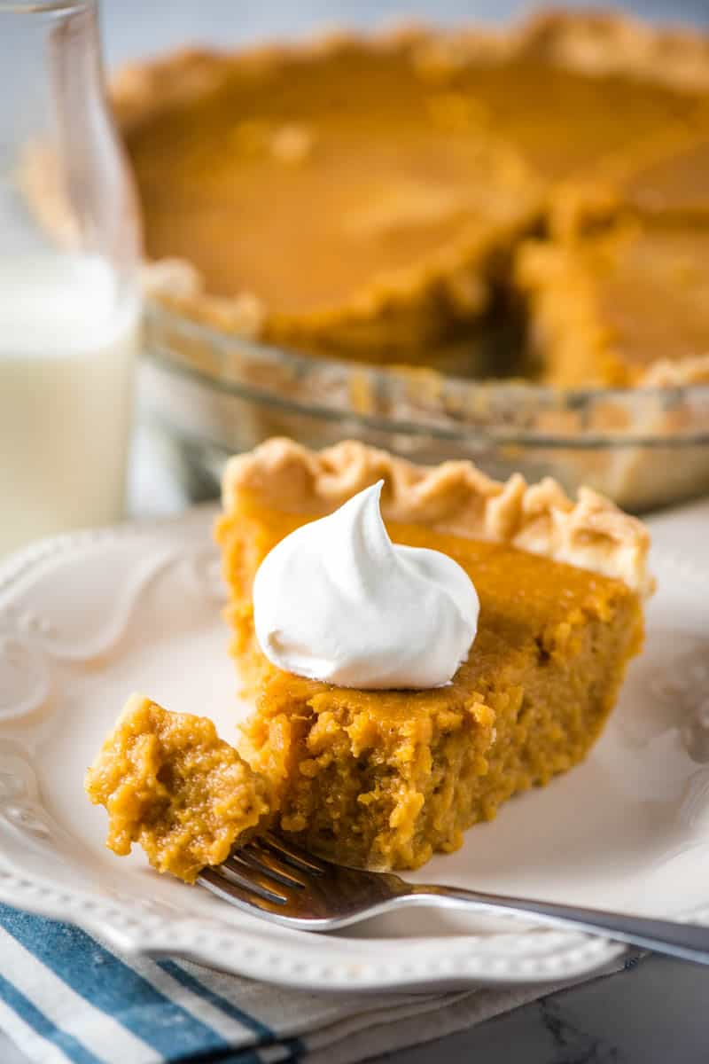 slice of southern style sweet potato pie on white plate with dollop of whipped cream, fork, and bottle of milk