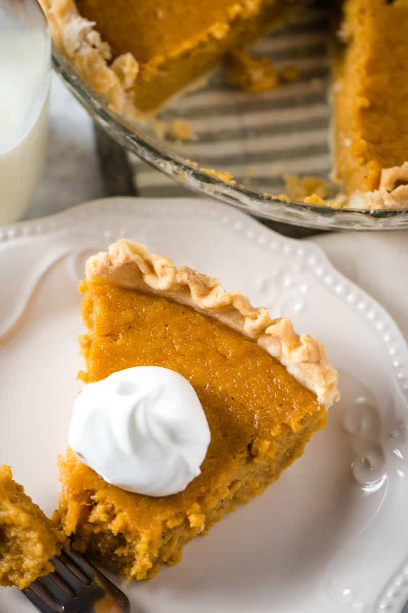 slice of sweet potato pie recipe on white plate with full pie and glass of milk