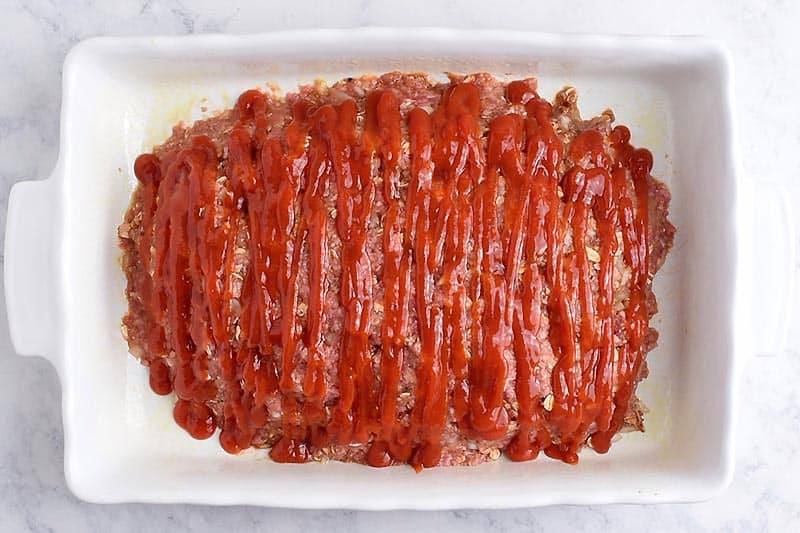 unbaked oatmeal meatloaf covered with ketchup in a white baking dish