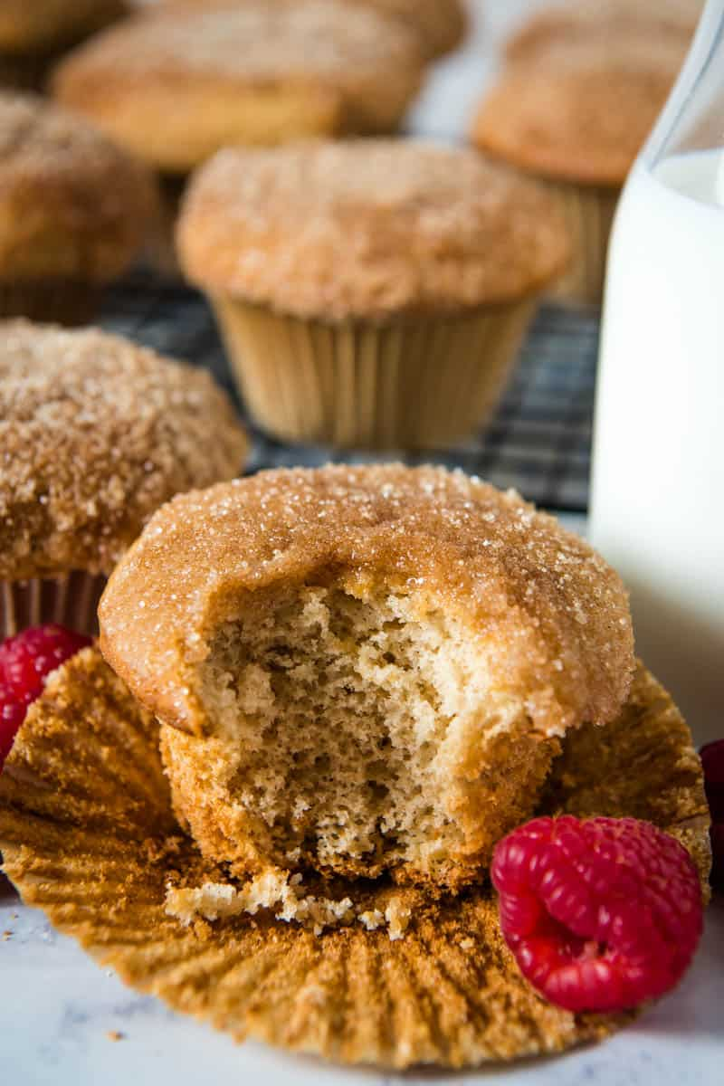 bite out of Bisquick cinnamon muffin sitting on cupcake liner with fresh raspberries and milk in a glass