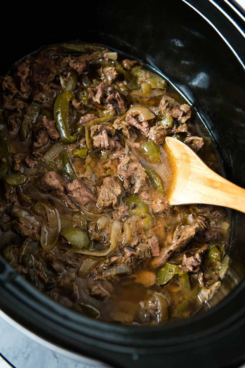 sirloin steak cooked in black Crock Pot slow cooker with onions, green bell peppers, garlic, Worcestershire sauce, and beef broth