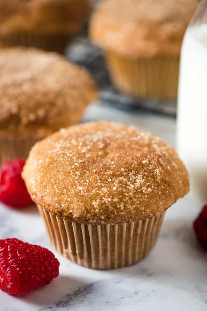 easy cinnamon muffins sitting on white marble countertop with fresh red raspberries and glass of milk