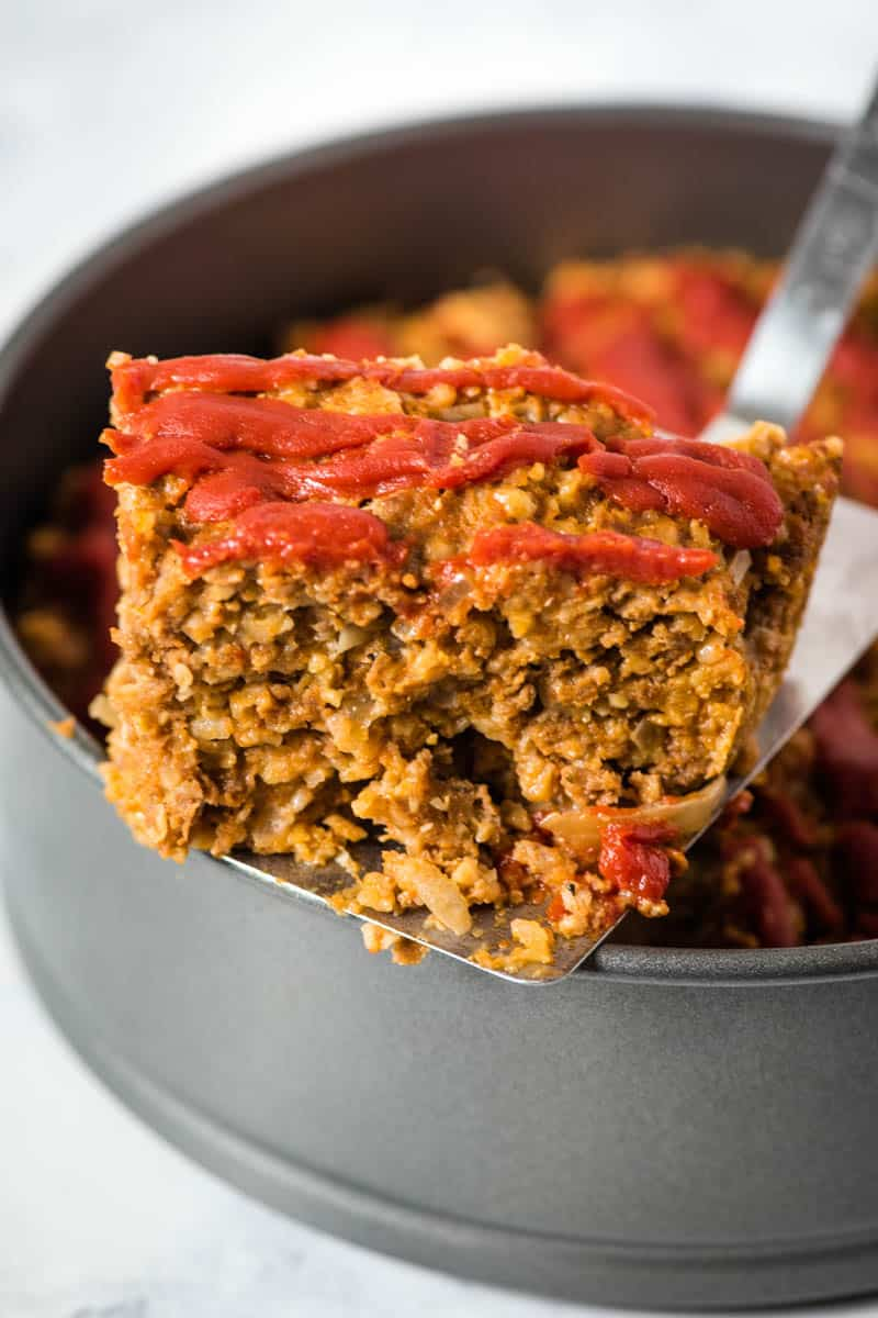 slicing and serving Instant Pot meatloaf with oatmeal from springform pan with metal spatula flipper