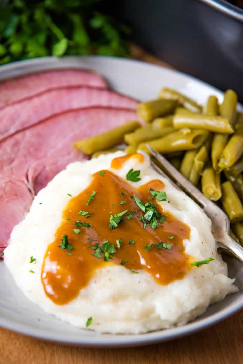 ham gravy with cornstarch on mashed potatoes, served on grate plate with baked ham, green beans, and a fork