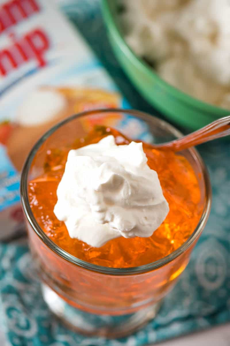Orange Jello topped with Dream Whip whipped topping in glass dish with spoon on teal blue napkin with Dream Whip box