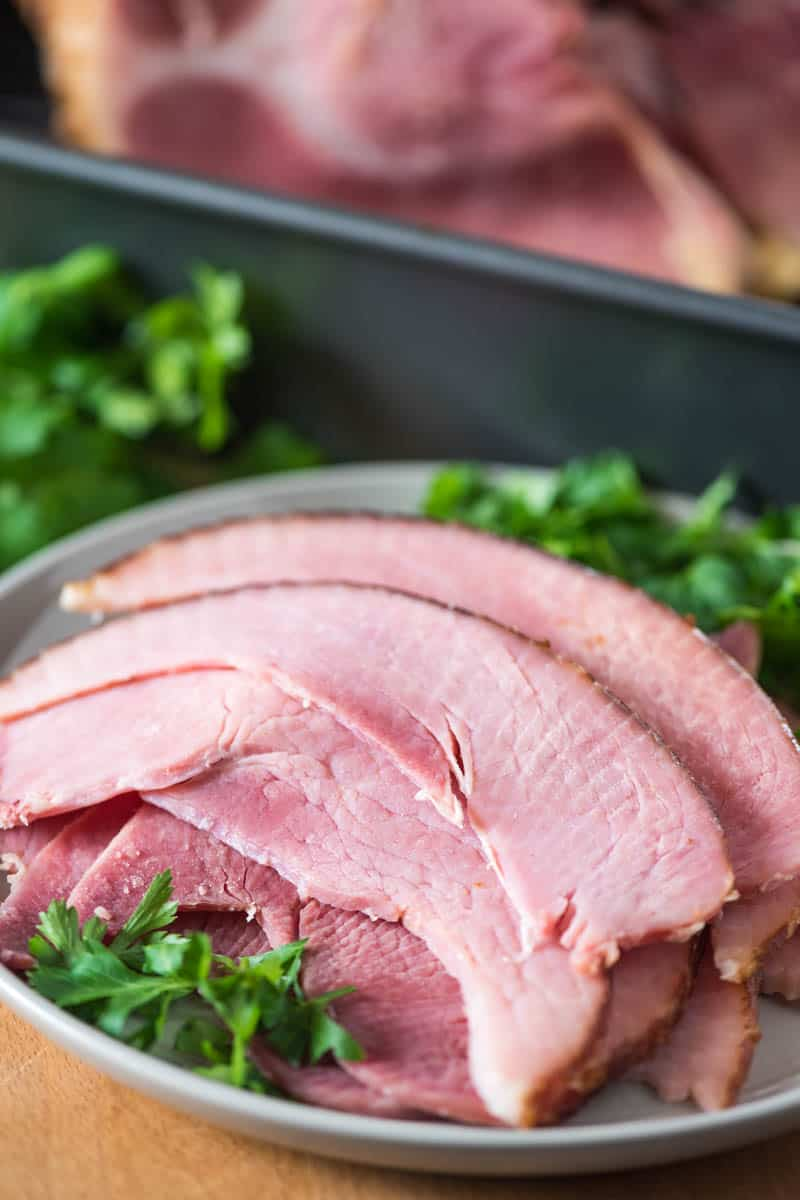 sliced ham on gray plate with Italian parsley