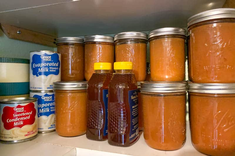 best survival food like home canned applesauce, evaporated milk, and honey on white shelves
