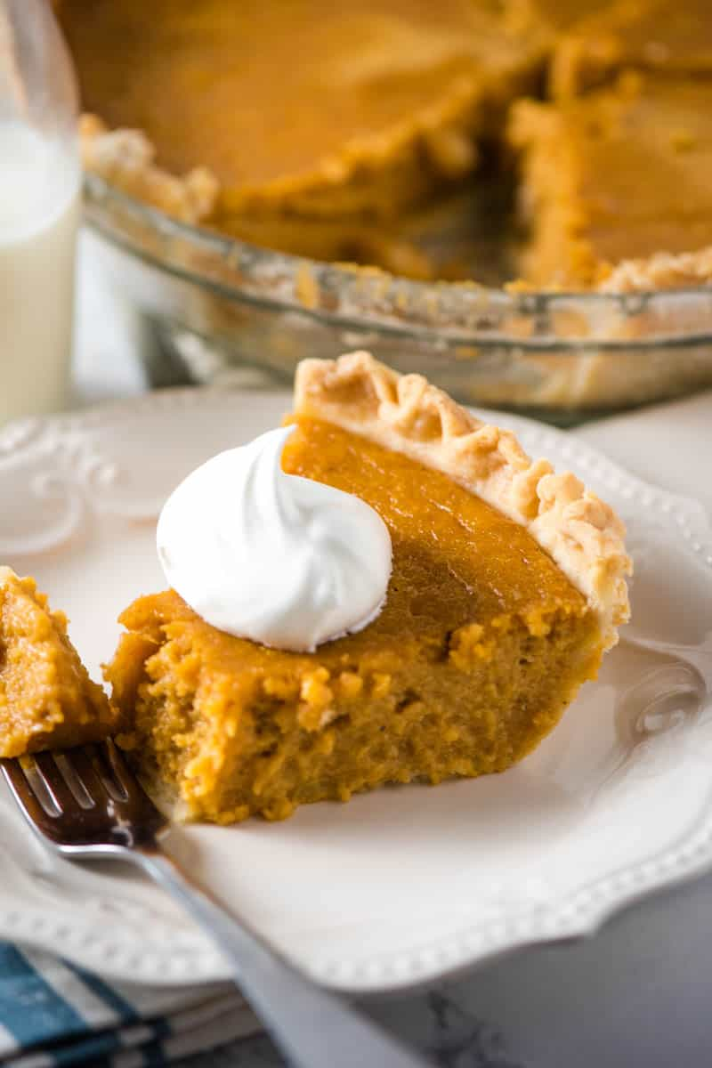perfect pie crust with sweet potato pie filling and whipped cream on white plate with fork