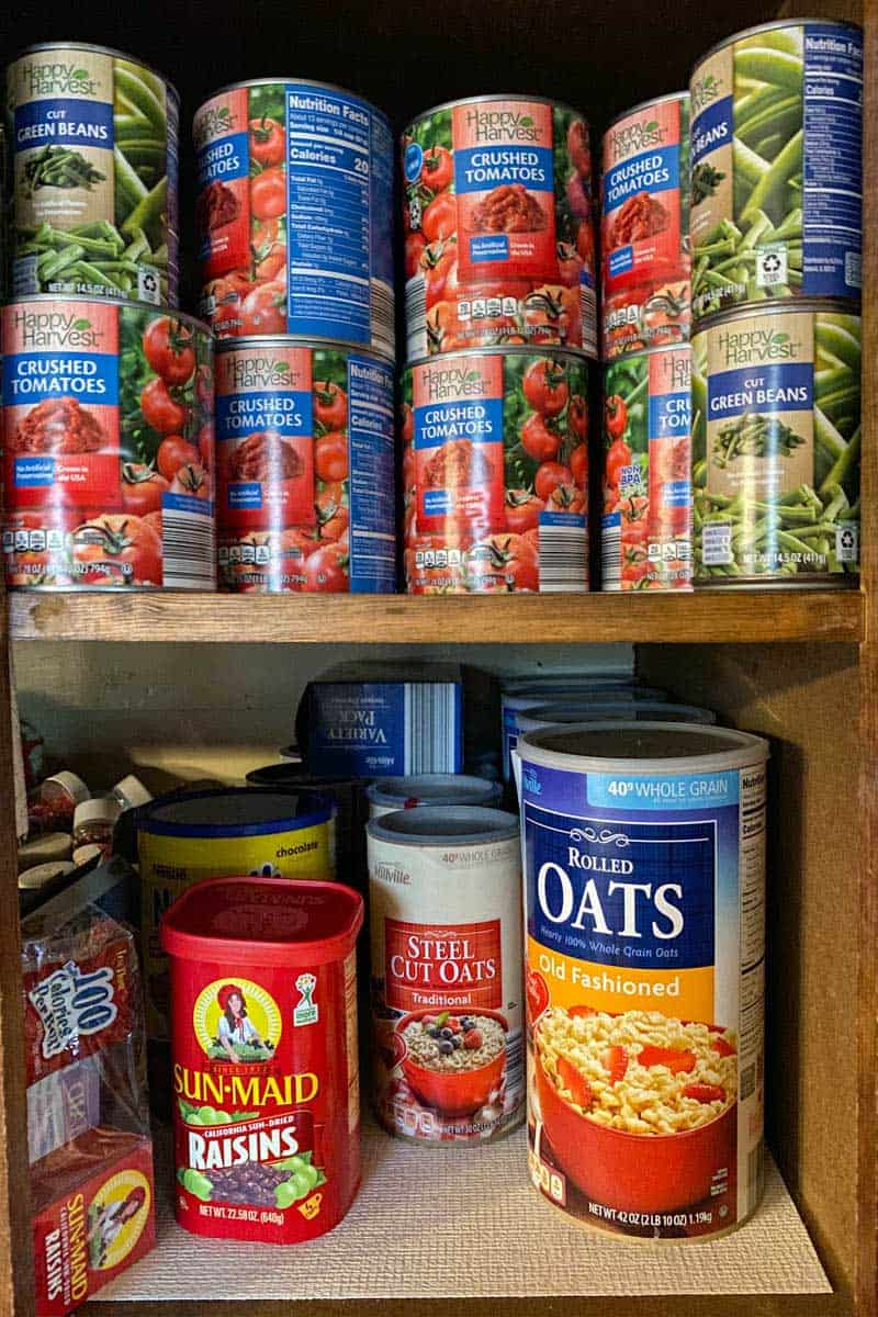 shelf-stable canned foods and survival foods in cabinet, including crushed tomatoes, green beans, oats, and dried fruit