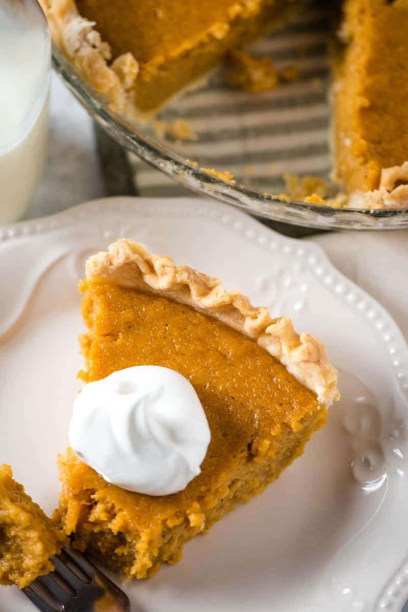 slice of sweet potato pie with homemade pie crust and whipped cream on white plate with fork