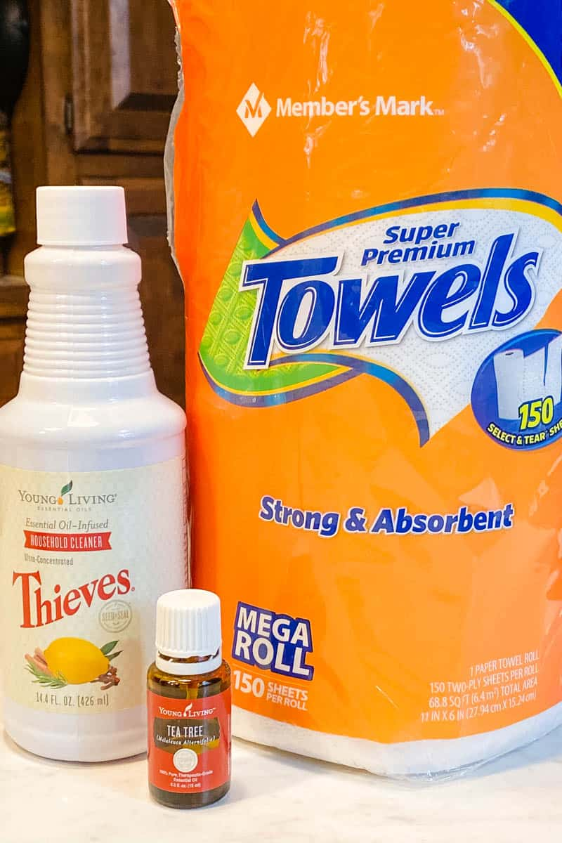 Thieves wipes ingredients, including paper towels, Thieves Household Cleaner, and Young Living Tea Tree oil on white countertop