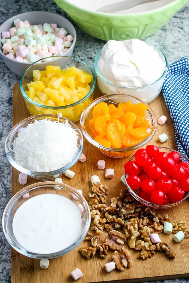ambrosia ingredients, including cherries, whipped cream, mandarin oranges, pineapple tidbits, coconut, sour cream, multi-colored mini marshmallows, and nuts in small glass bowls on wooden cutting board