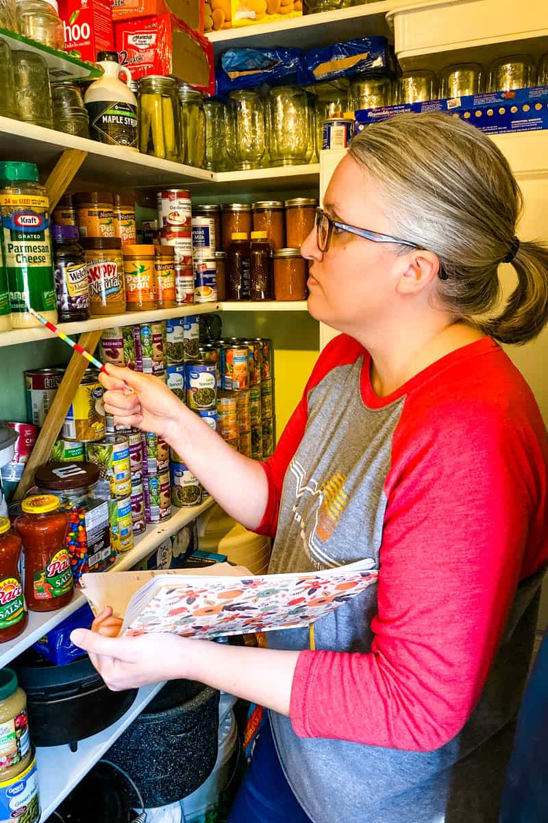 woman taking inventory of pantry staples with pencil and notebook in home working pantry