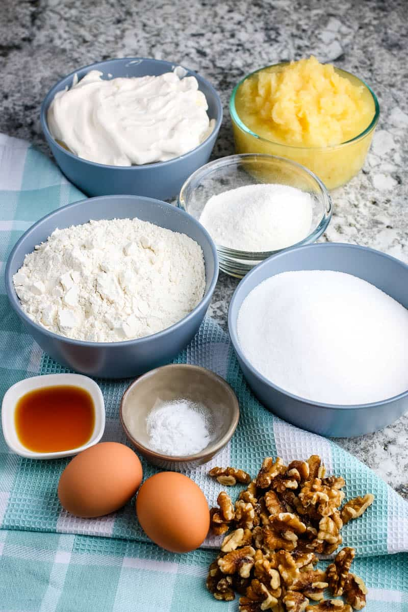 pineapple cake ingredients, including flour, sugar, baking soda, eggs, vanilla extract, crushed pineapple, walnuts, whipped cream, and vanilla pudding mix