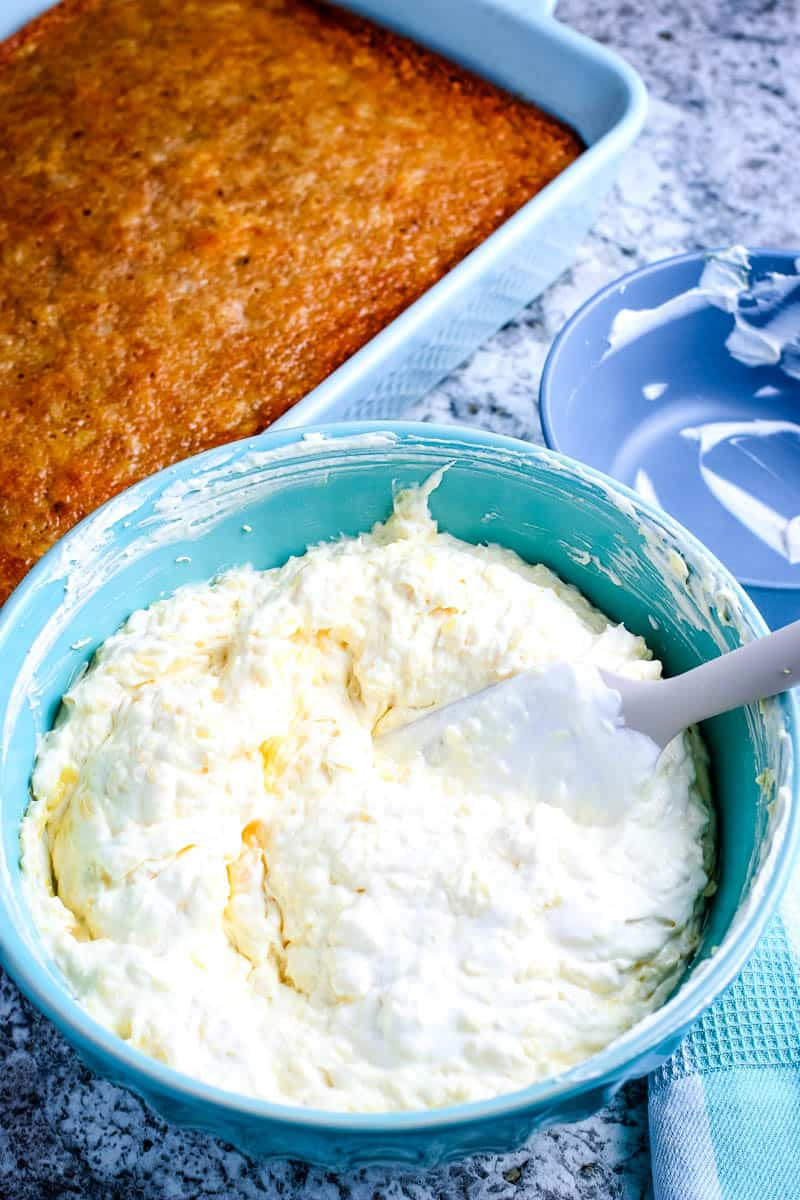 easy pineapple cake in light blue cake pan with teal bowl of whipped pudding topping and spatula