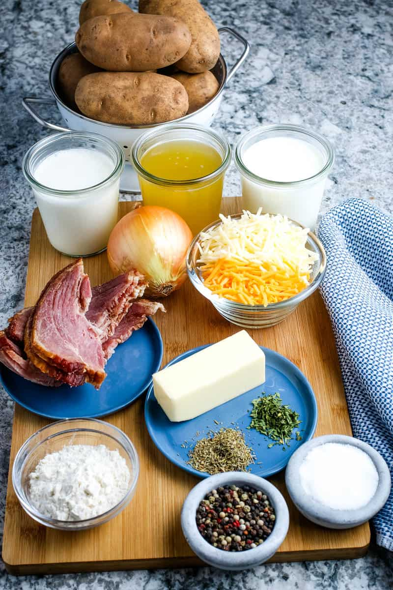 ingredients for scalloped potatoes and ham recipe, including potatoes, heavy cream, milk, chicken broth, yellow onion, cheddar cheese, Monterey Jack cheese, ham, butter, thyme, parsley, salt, pepper, and flour