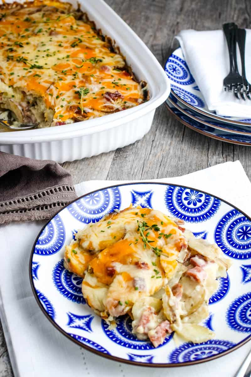 serving of scalloped potatoes and ham casserole on blue and white decorative plate with whole casserole in white casserole dish behind plate, along with more plates and forks for serving