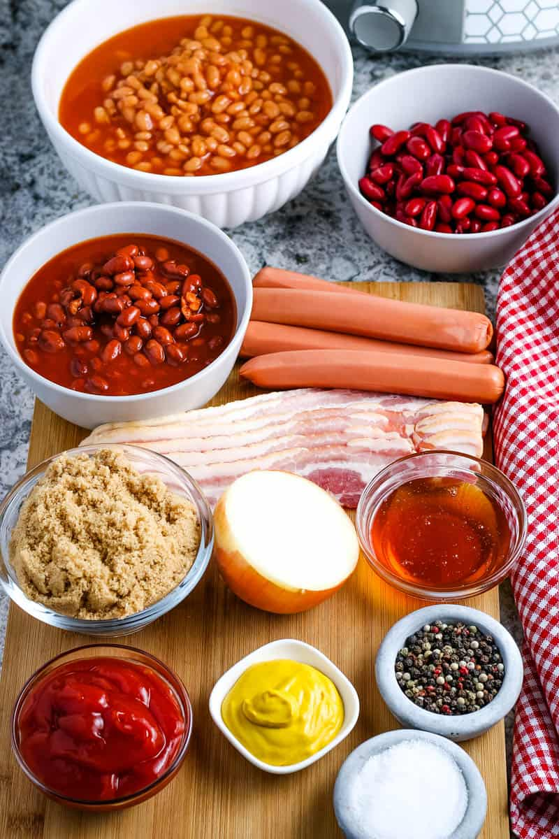 ingredients for baked beans in various bowls on wooden cutting board, including pork and beans, red kidney beans, chili beans, hot dogs, bacon, brown sugar, yellow onion, honey, ketchup, yellow mustard, salt, and pepper