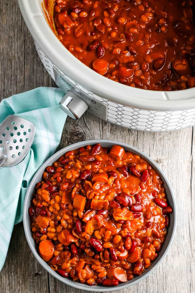 CrockPot baked beans in white slow cooker and dished out in gray bowl on wooden countertop with light teal kitchen towel and serving spoon