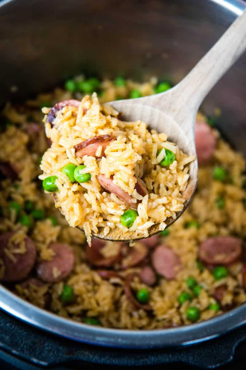wooden spoonful of Instant Pot smoked sausage and rice with green peas over pressure cooker full of rice