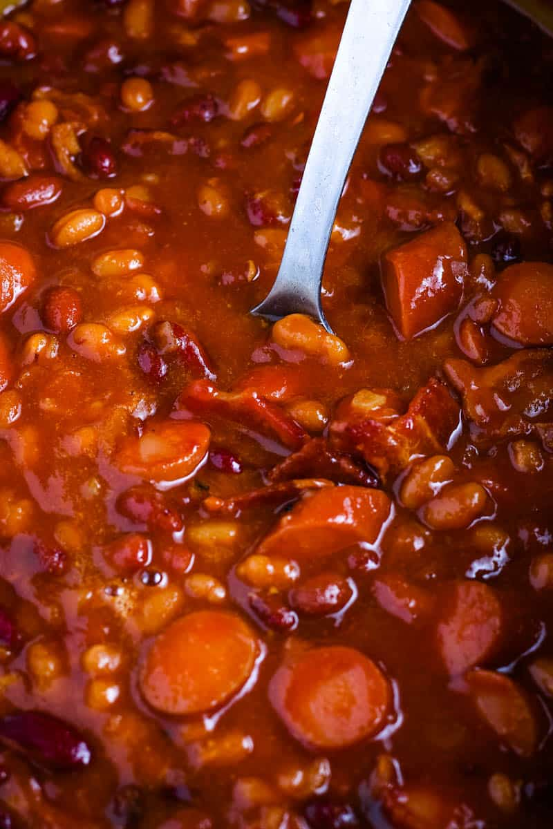 close up picture of slow cooker baked beans with spoon
