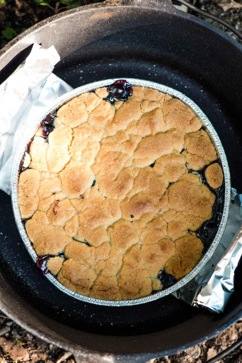 baked sugar cookie cobbler in round foil pan inside cast iron Dutch oven with foil sling