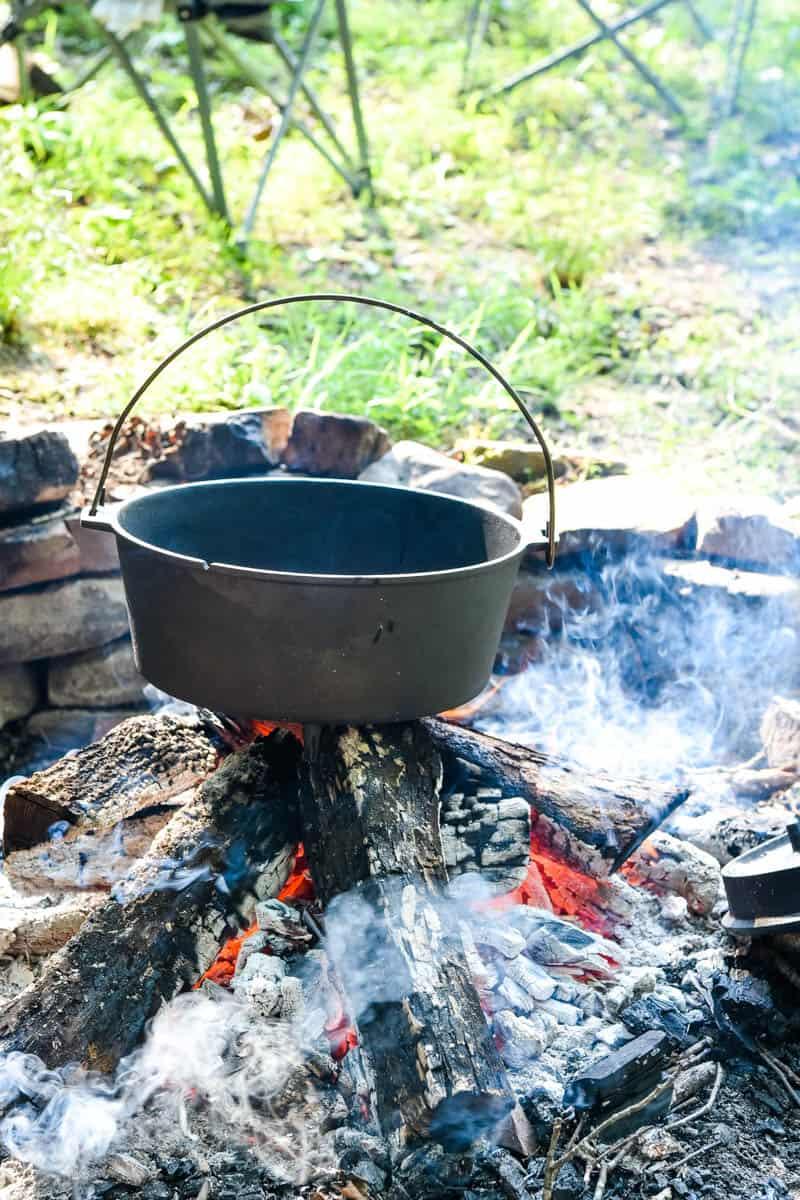 Dutch oven pre-heating over campfire coals