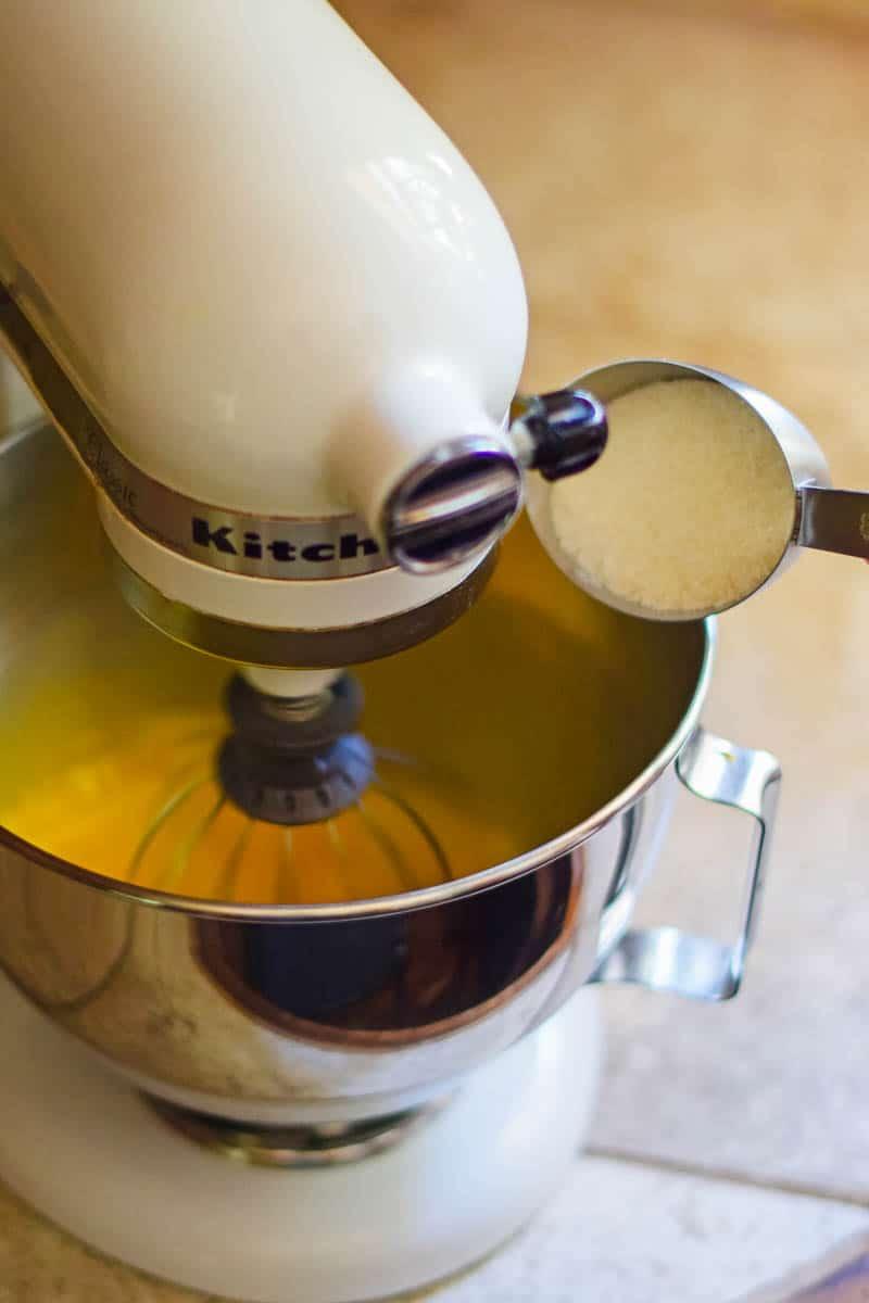 adding sugar to eggs in metal bowl of white KitchenAid mixer