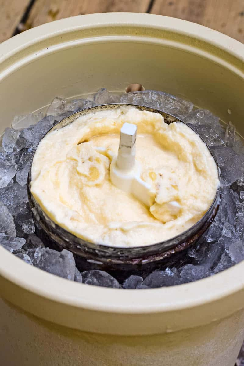 old-fashioned banana ice cream frozen and ready to eat with churn paddle in metal ice cream canister, placed down in plastic ice cream maker tub full of ice and rock salt